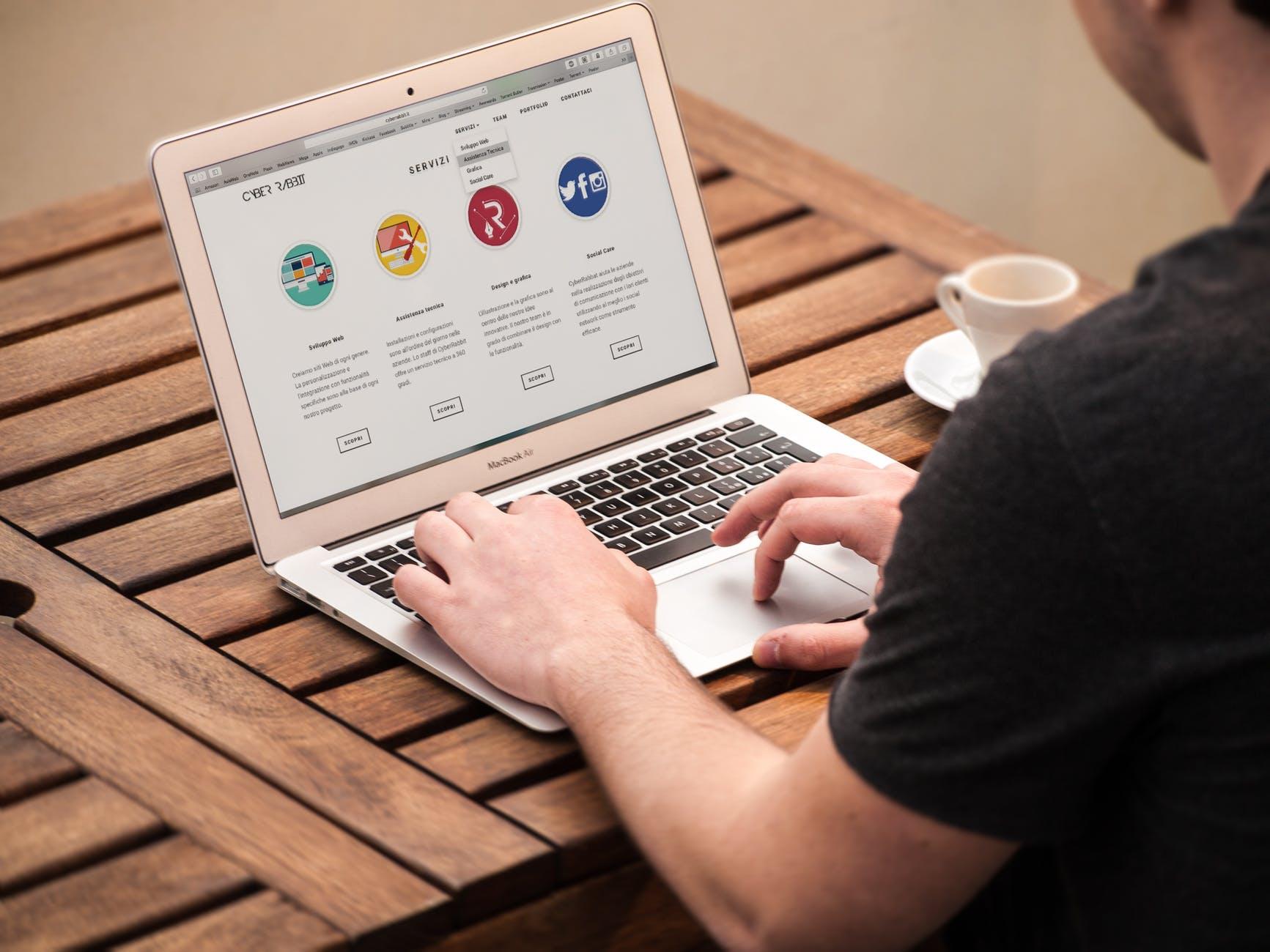 Barbat la laptop navigand pe internet